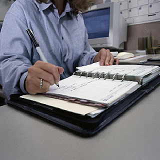 woman filling out diary at desk