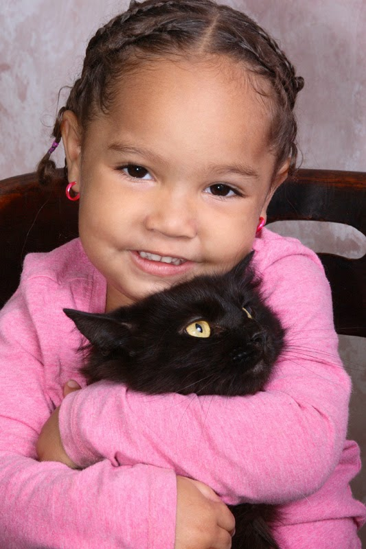 A happy young girl cuddles her black cat