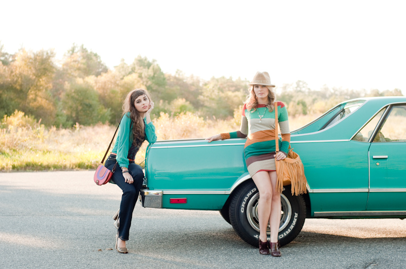 Two chic girls standing by a classic car