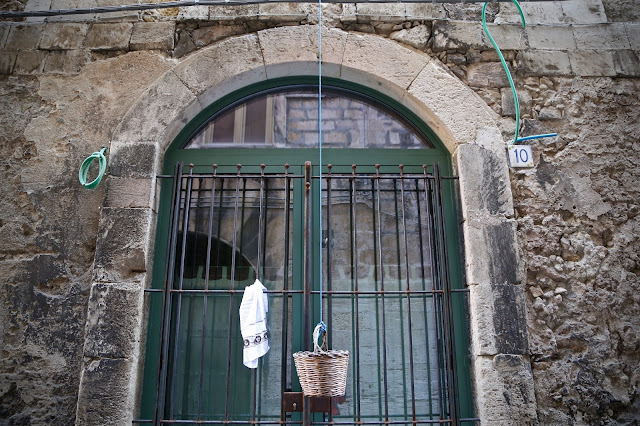 Shopping baskets hanging in the street, in Italy, Catania, Sicily,