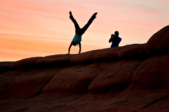 A girl doing a handstand during sunset while her boyfriend takes a photograph.