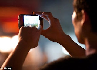 Photo taken from behind a person filming a scene with a smart-phone.