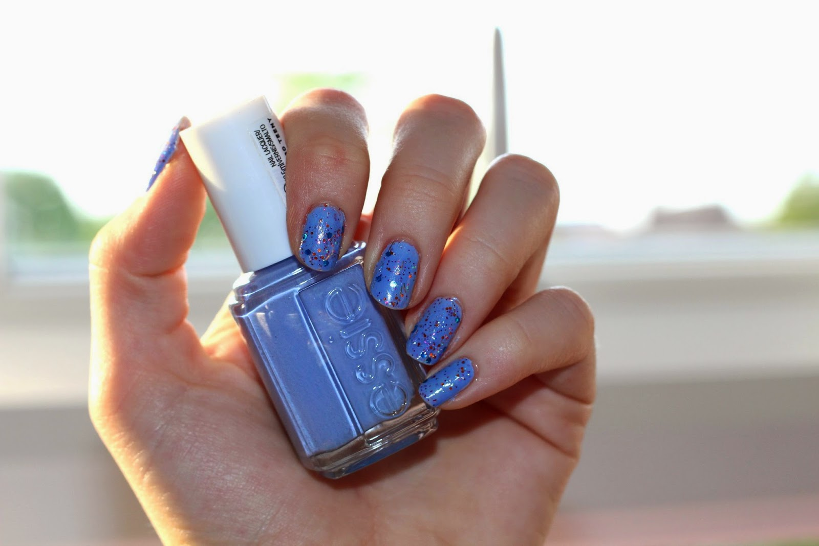 A close up picture of a nail swatch holding a bottle of Essie Bikini So Teeny