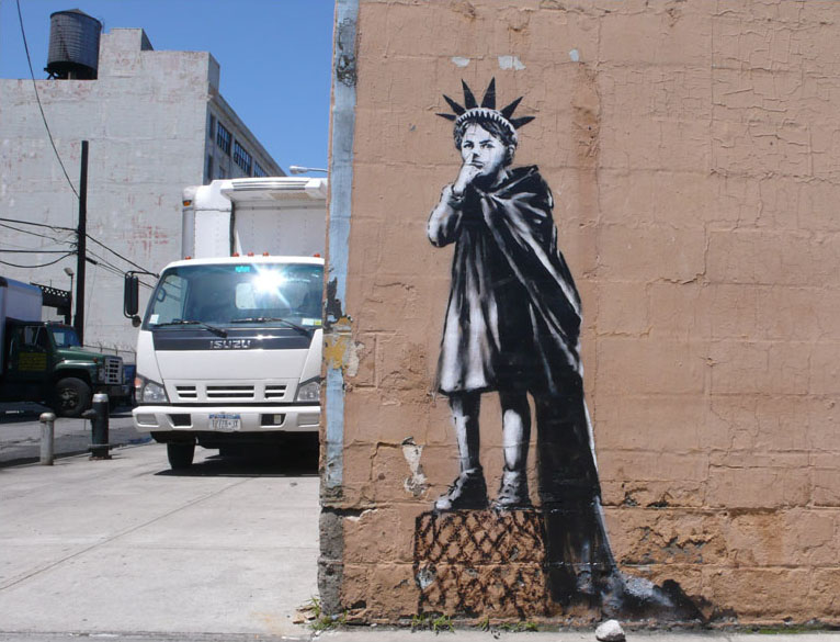 street art by Banksy - boy dressed as statue of libery picking his nose