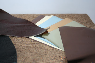 a photo of brown and black leather scraps and a selection of metallic transfer foils.