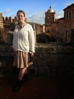 A woman in a cream cardigan and brown dress standing in front of the Toledo-Moctezuma tower in Caceres