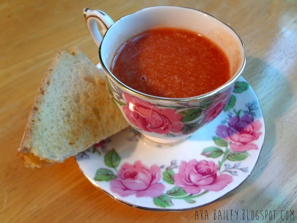 Tomato bisque and grilled cheese wedge, served on a teacup