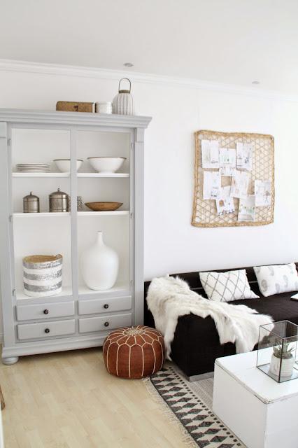 graue Vitrine ohne Türen mit diverser weißer und silberfarbener Deko daneben schwarzes Sofa mit Kissen und Fell