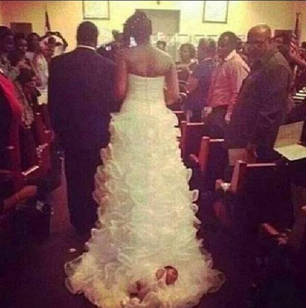 Un bébé attaché à la traîne de sa robe de mariée