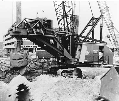 A 6-foot- (1828-mm)-diameter auger on a telescoping 70-foot (21-m) bar brings up a load of soil from a caisson hole. The auger will be rotated rapidly to spin off the soil before being reinserted in the  hole.