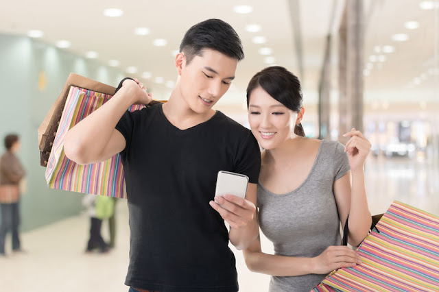 A couple walks through a mall, hands filled with shopping bags, searching for their next destination on their smartphone.
