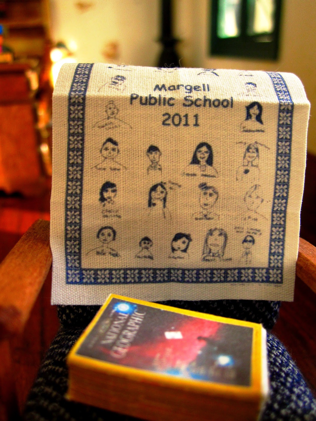 Close up of a 1950s-style miniature chair, displaying a 2011 fund-raising tea towel for Margell Public School and a stack of old National Geographic magazines.