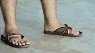 Os pés masculinos do ator Thiago Lacerda usando chinelos Cartago