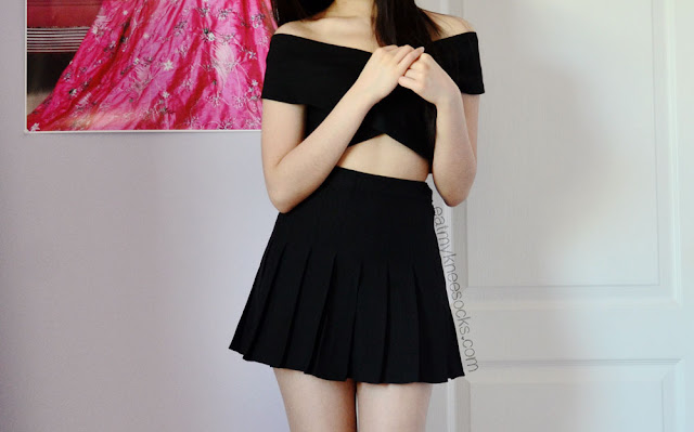 This off-shoulder short sleeve black crop top has a wrap style and zippered back.