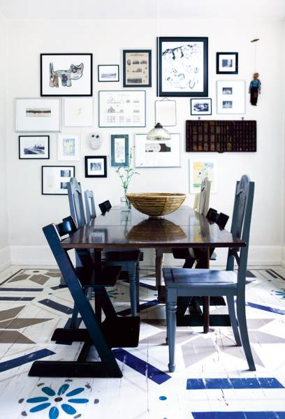 Dining room with dark wood table surrounded by mismatched blue chairs, the white wall in the back is covered with art in different sizes in blue frames, and a single pendant light. The white wood floor is painted with a variety of blue, brown and grey graphic patterns