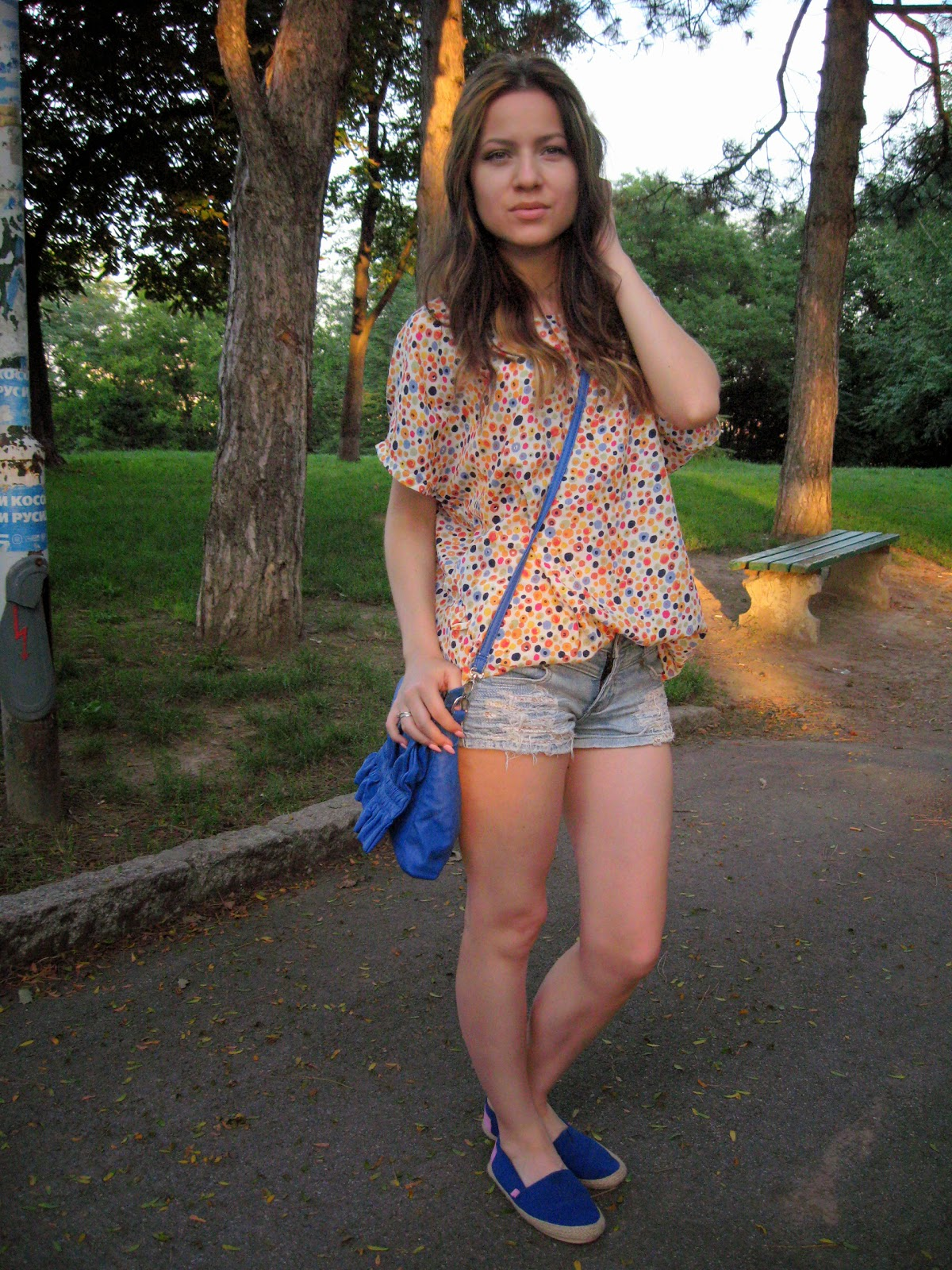 cobalt blue espadrilles, cobalt blue over the shoulder bag, floral top with crochet details on the back, blue denim shorts, hairstyle with highlights front layers, pale pink baby pink stiletto nails
