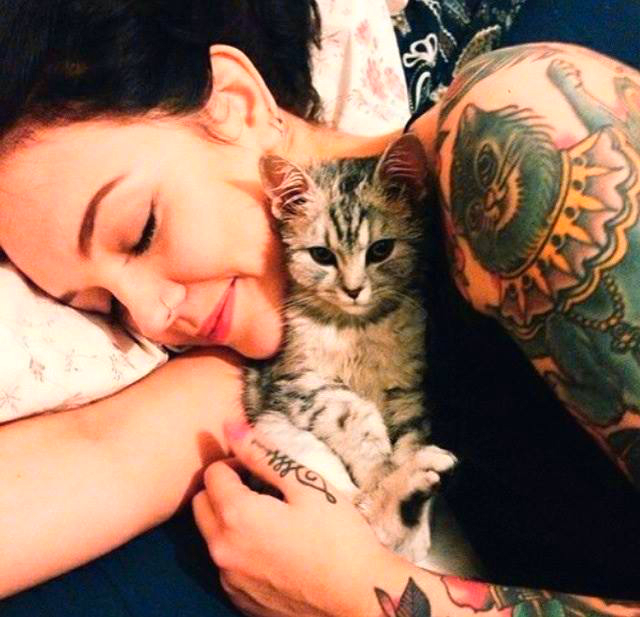 chica con tatuaje de gato en el hombro esta abrazada a un gatito