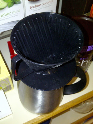 Shows plastic cone on top of coffee cup