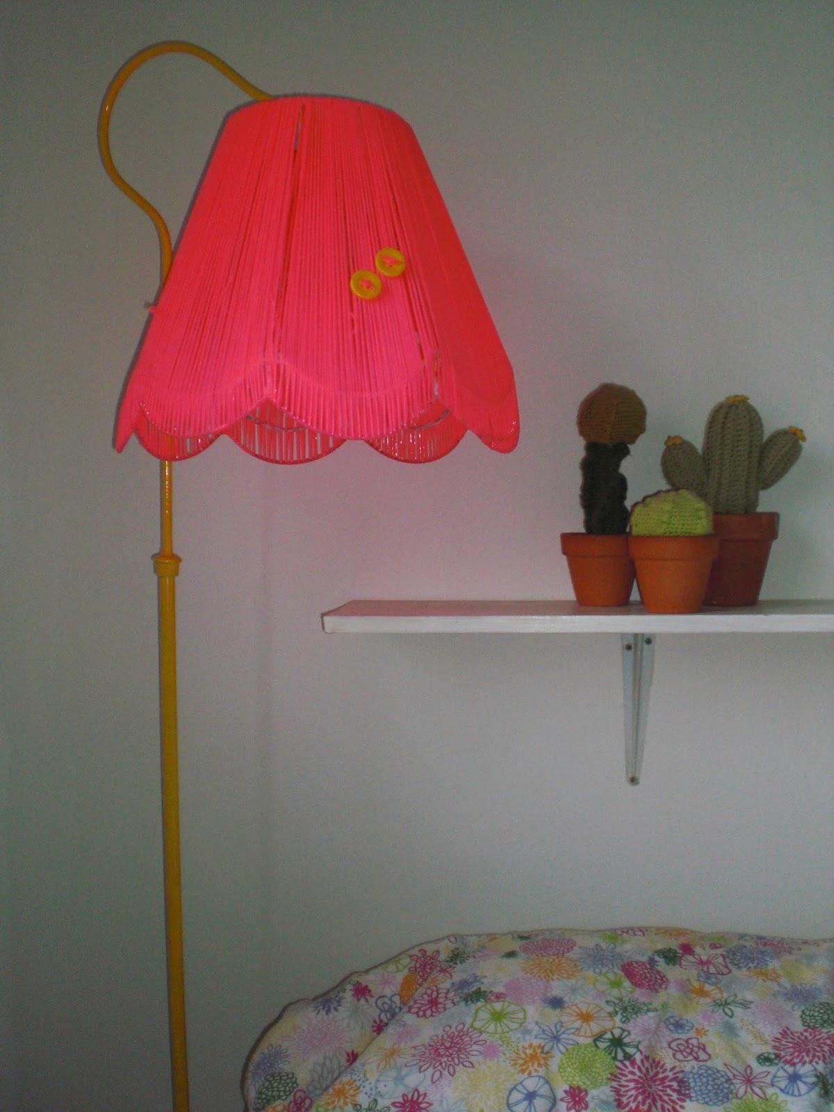 Gul standerlampe med neonpink lampeskærm.