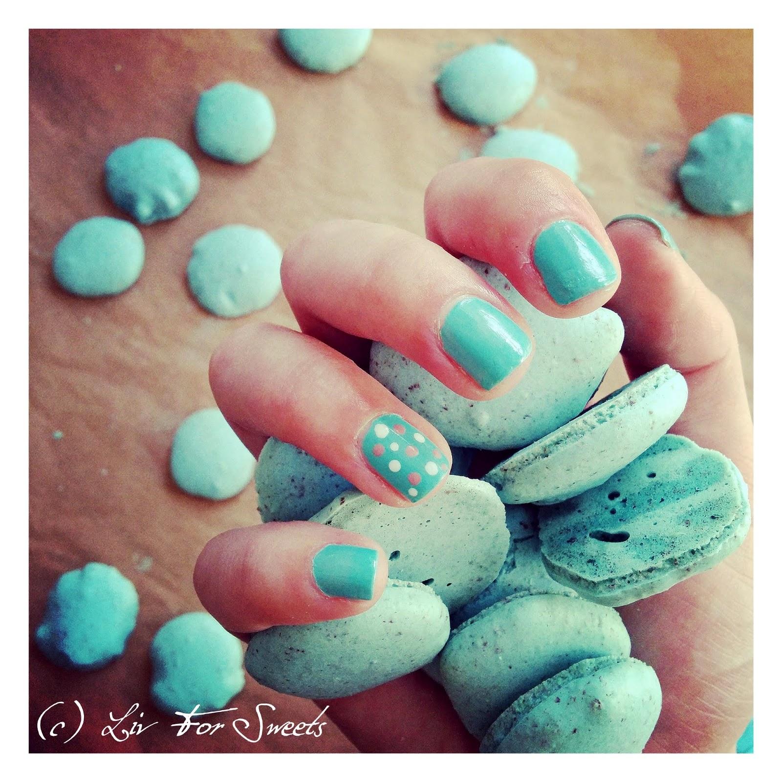 Macarons in der Farbe türkis / teal / hellblau in einer Hand mit türkisem Nagellack