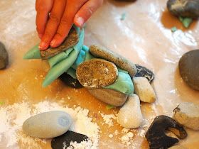 boy building with play dough and rocks