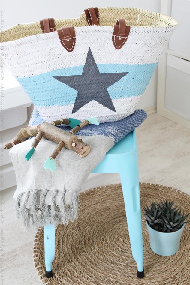 Korbtasche w eiß mit hellblauem mittigen Streifen darauf ein anthrazitfarbener Stern auf einem türkisen Hocker mit Plaid in blau beige für den Bloggeroptimierungsfotowettbewerbbeipixum
