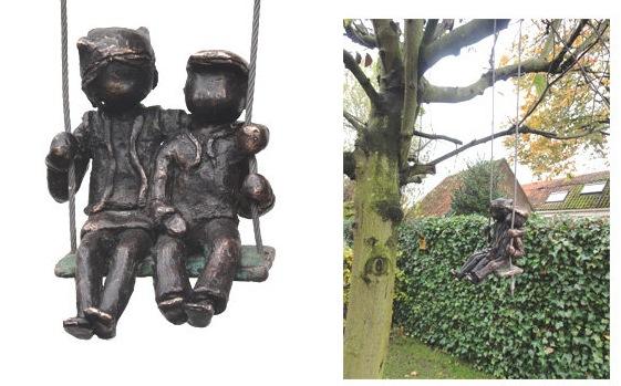 Bronze children on a swing in the garden