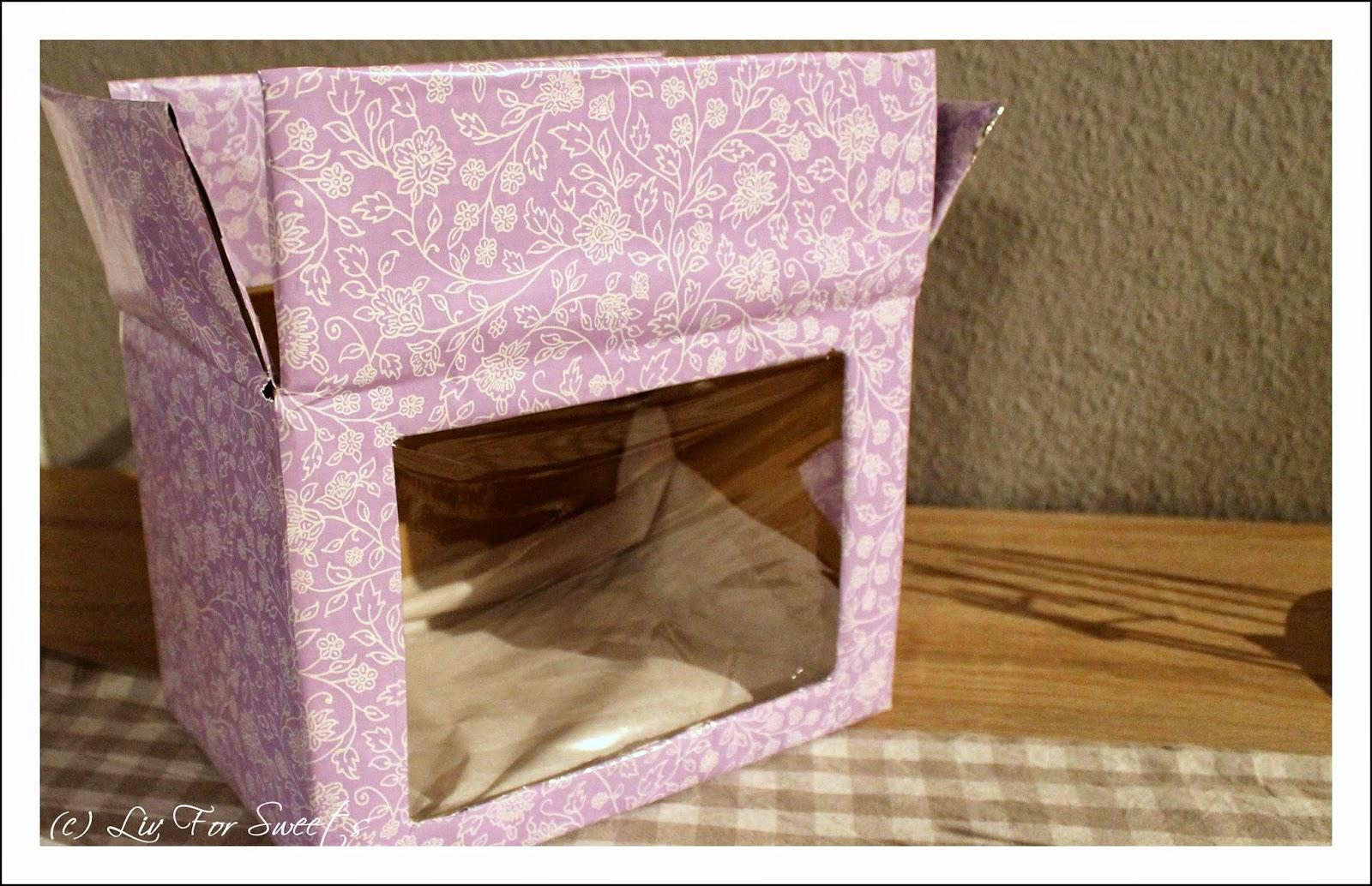 Eine selbstgebastelte Box in lila für den Transport von Cake-Pops