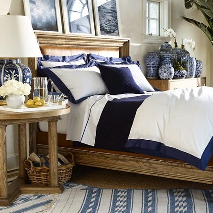 Duże łóżko z granatową pościelą i ramkami na ścianie