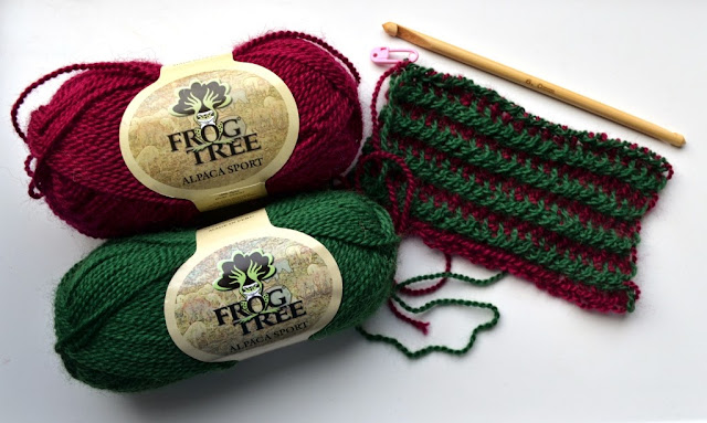 Two skeins of Frog Tree Alpaca Sport yarn  in deep magenta (#26) and bottle green (#43) on the left hand side connected to the striped scarf on the right. Above the scarf is a 6.0 mm diameter, 15 cm long, double-ended bamboo hook. A pink stitch marker in the shape of a safety pin keeps the active loop in magenta yarn secure at the top left corner of the scarf.