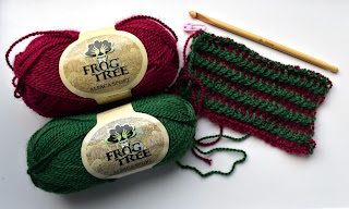 Two skeins of Frog Tree Alpaca Sport 100% alpaca yarn next to my scarf in progress which is made of alternating green and dark red stripes. The bamboo crochet hook is alongside the scarf in the top right hand corner of the photograph.
