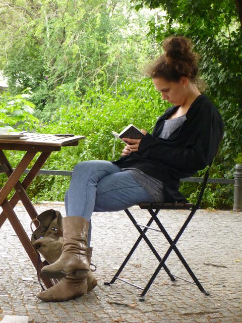 Eine Frau sitzt auf einem Holzklappstuhl an einem Holzklapptisch und liest, hinter ihr ein Weg und viel Parkgrün