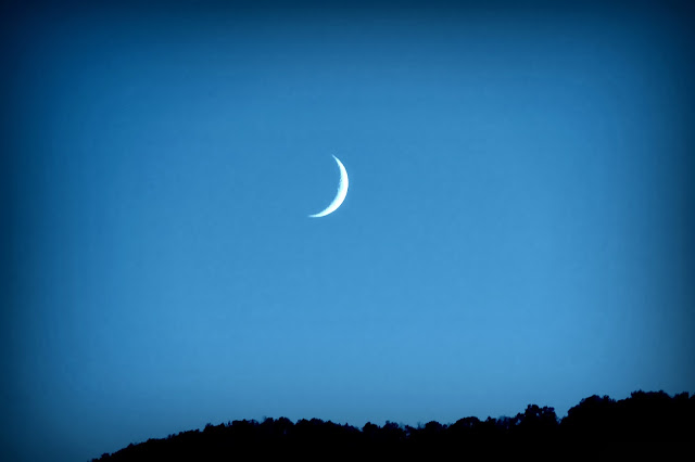 waxing crescent moon on a blue sky over a moutain ridge