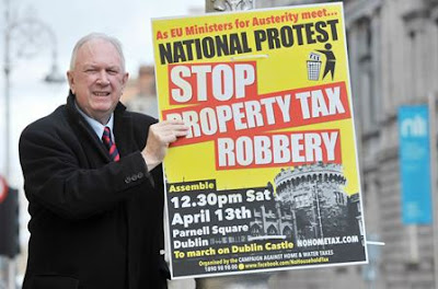 A man puts up a poster outside Leinster House in Dublin, to promote an anti-property tax protest in Dublin city center 