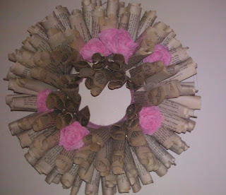 image of rolled book pages fashioned into a wreath with pink flowers