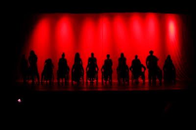 Elenco do musical Filhos do Brasil em silhueta no palco sobre um fundo iluminado de vermelho; cadeirantes lado a lado e atrás de cada cadeira um ator andante.
