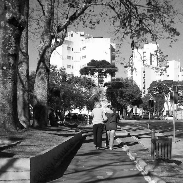 Fotografia P e B. No centro da imagem uma pista de caminhada numa praça ensolarada. De costas, caminham na pista, de braços dados, uma mulher idosa de cabelos curtos e menina de cabelos longos e presos. Usam agasalhos, moletons, tênis. À esquerda da pista, canteiro alto com gramado, três troncos grossos de árvores enfileirados e à direita, canteiro baixo com gramado, lixeira, calçada e via pública. Ao fundo, árvores, copas arredondadas, uma araucária, veículos estacionados, prédios altos, céu sem nuvens.