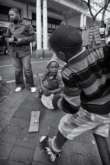 A South African boy drums for change while another boy makes a dart into the frame in this Cape Town street photo