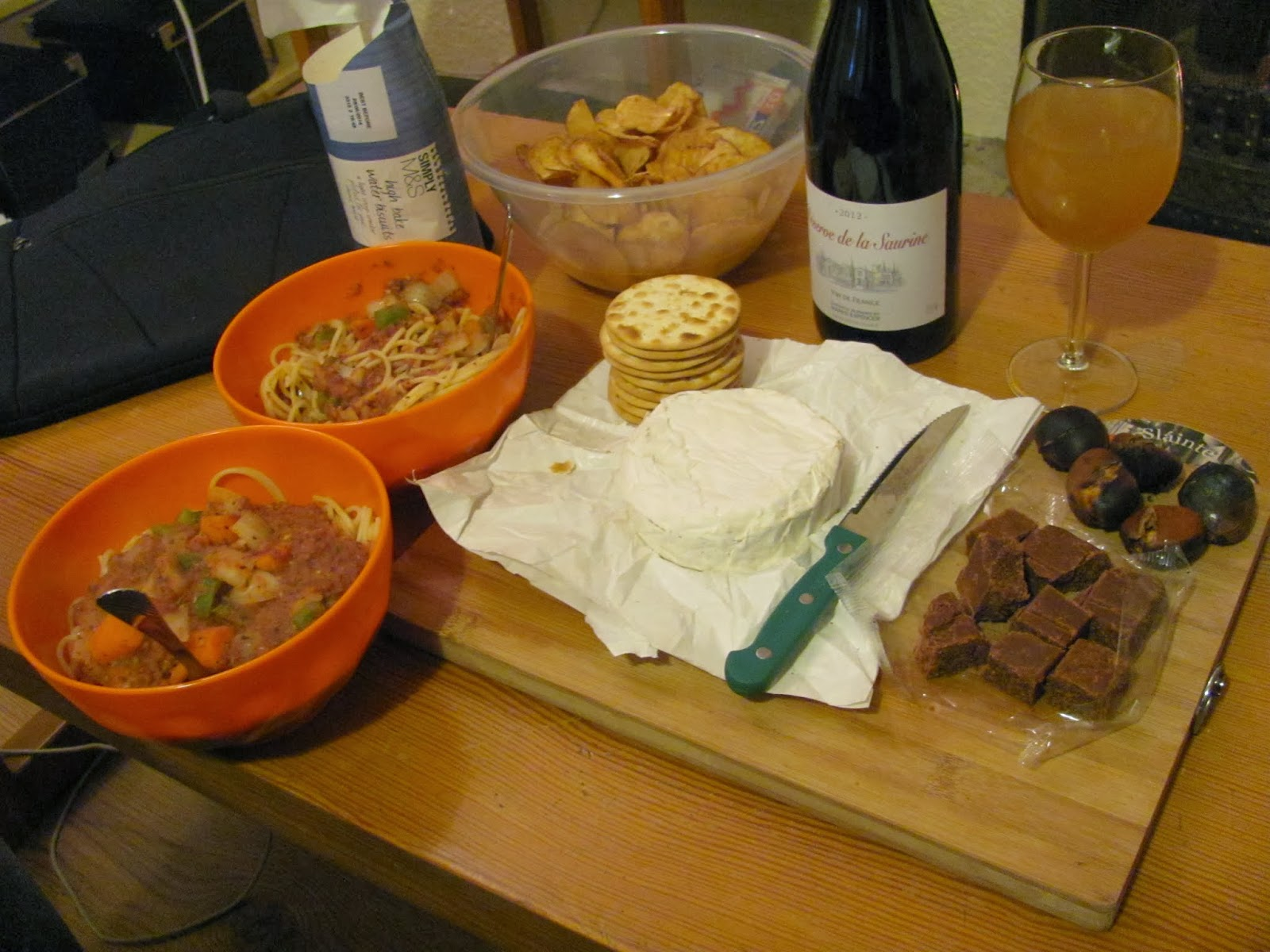 The full spread of cheese, fudge, crackers, wine, cider, pasta, chestnuts, and potato crisps