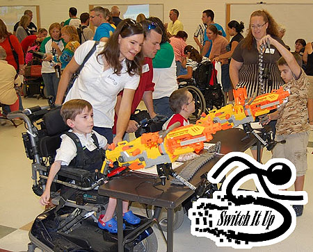 Photo of children using switch adapted Nerf guns, and games in the back ground, linked to the new Switch It Up! accessible gaming event.
