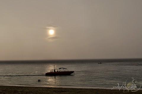 Boat cruising against a romantic sunset and rain at Puerto Galera white beach.