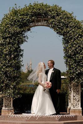 wedding couple under arch, cinderella castle in distance