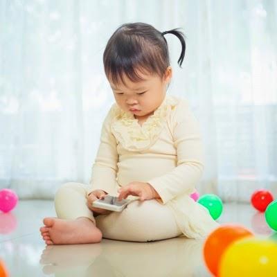 Aqui tem a imagem de uma criança utilizando o celular