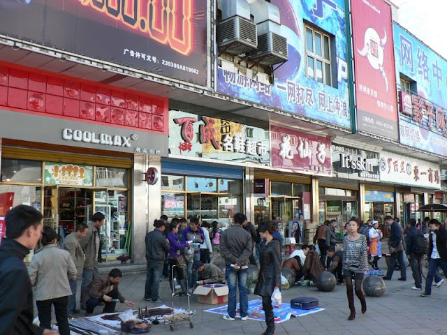 people selling items on a shopping street