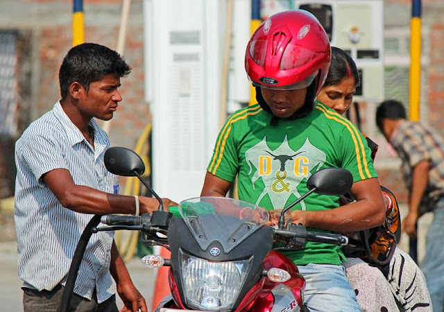motor bike rider paying cash for gas