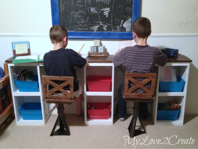 kids sitting at the desk trying out chairs
