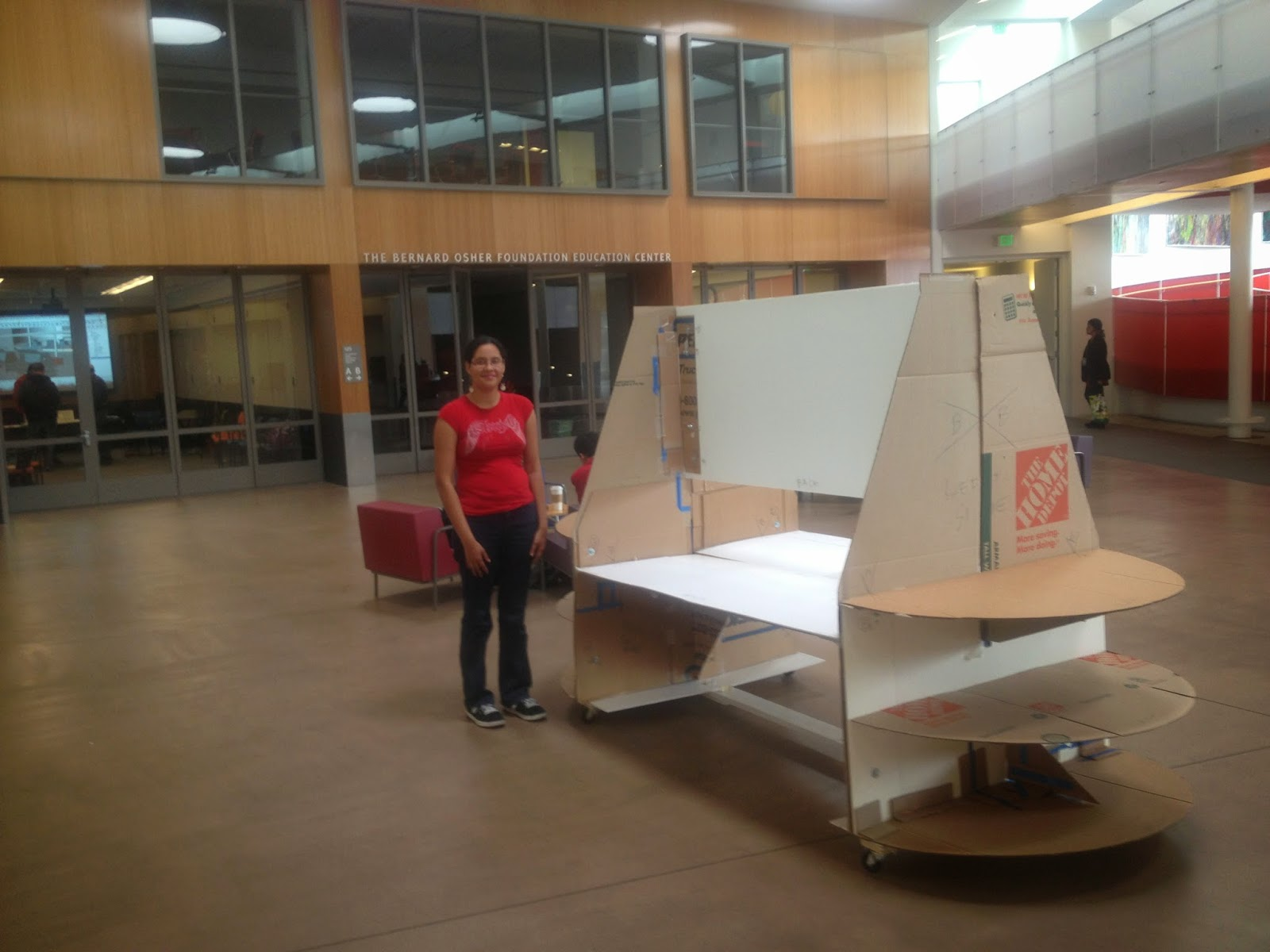 A student is standing to the right of the cardboard model within the Ed Roberts Building.