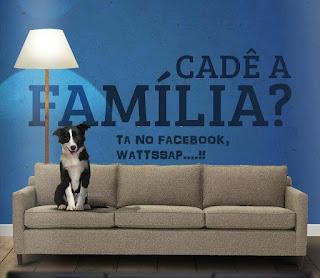 Foto de um sofa marrom claro de três lugares, sentado na primeira almofada à esquerda, um cão da raça border collie, sozinho. Próximo à parede azul atrás do sofa, uma luminária alta, com cúpula branca, ilumina as letras enormes pretas e lê-se: Cadê a Família? E abaixo, em letras menores: Ta no Facebook, Wattssap....!!