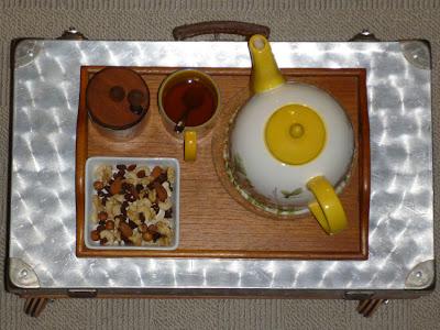 """Metallkoffer-""""Tisch"""" mit Holztablett, darauf eine Kaffeekanne, eine Teetasse, Honig und ein Schälchen mit Studentenfutter"""