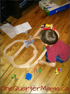 Little Man playing with Imaginarium train set OneQuarterMama.ca
